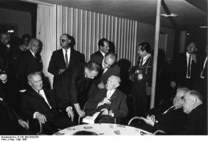 Goldmann, Adenauer, and Ben-Gurion, with Moshe Dayan in the background (c) Bundesarchiv, B 145 Bild-P092350 / CC-BY-SA 3.0 / https://creativecommons.org/licenses/by-sa/3.0/de/deed.en